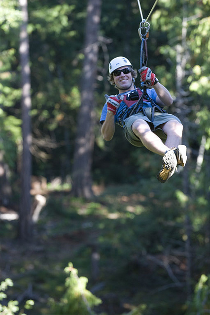 Man gives a thumbs up while ziplining down AdrenaLINE Zipline in Victoria.