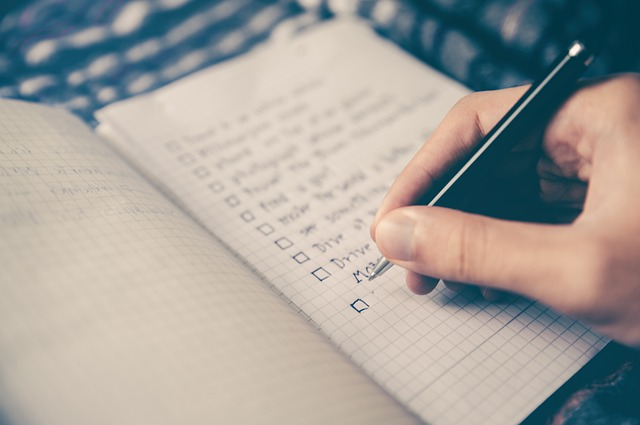 Photo of a hand writing a checklist in a gridded notebook. Photo credit Max Pixel.