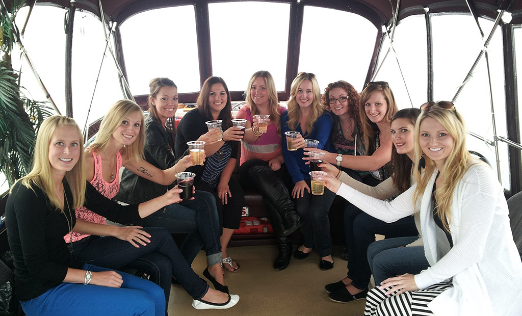 A bachelorette party comfortably seated on the Fantasea's upper deck raises their glasses to the camera.
