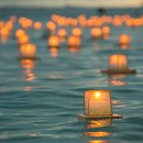 Paper memorial lanterns with well-wishes floating on the ocean off the shore of Honolulu, Hawaii.